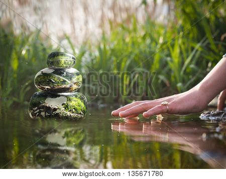 Transparent stones in water Zen pyramid. Stones of the volume inside the stones nature flowers. Children's or woman's hand above the water surface. Concept - peace of mind inner peace harmony poster