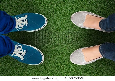 Man with canvas shoes on hardwood floor against close up view of astro turf