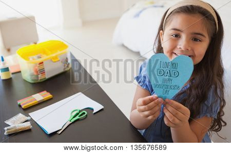 fathers day greeting against cute young girl holding heartshape paper at table