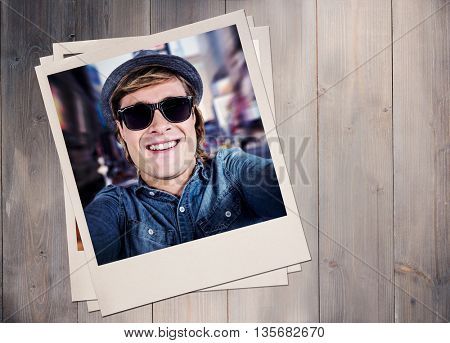 Crazy hipster wearing sunglasses against wooden planks