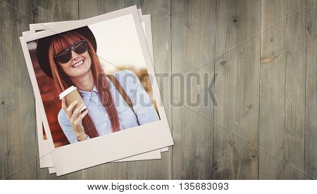 Smiling hipster woman drinking coffee against wooden planks