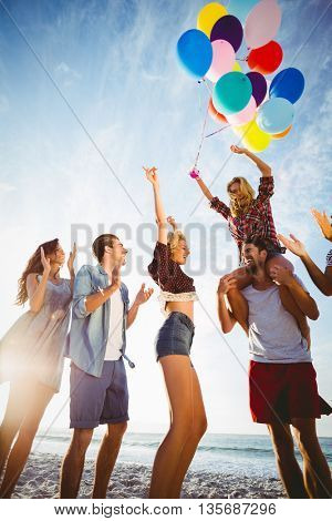 Friends dancing on sand with balloon on a sunny day