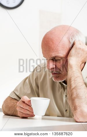 Tired Senior Man Sitting At Table Indoors