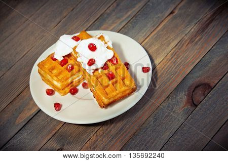 Traditional Belgian waffles with yogurt cream and pomegranate grains