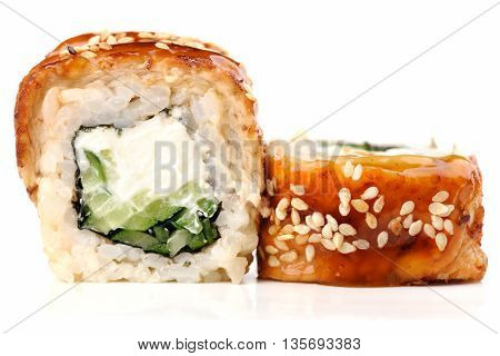 Sushi rolls with cream cheese nori and cucumber covered with eel sesame seeds and caramel sauce isolated closeup