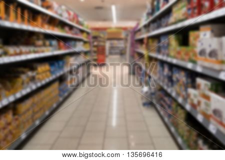 Supermarket shelves with various products out of focus vanishing point perspective.