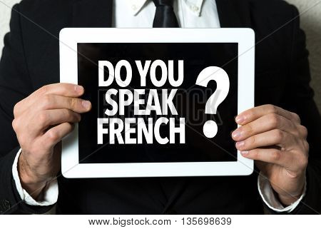 Business man holding tablet with the text: Do You Speak French?