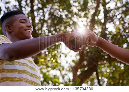 Youth culture young people group of male friends multiethnic teens outdoors teenagers together in park. Happy boys meeting kids shaking hands smiling. Concept of racism and integration of races