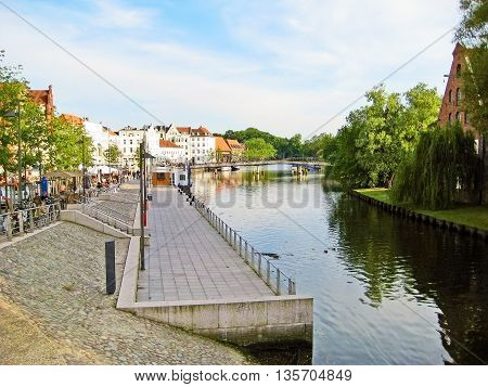 Luebeck Germany - May 23 2008: Promenade of river Trave in the historic city district (Altstadt) quay wall in front - near landmark Holstentor.