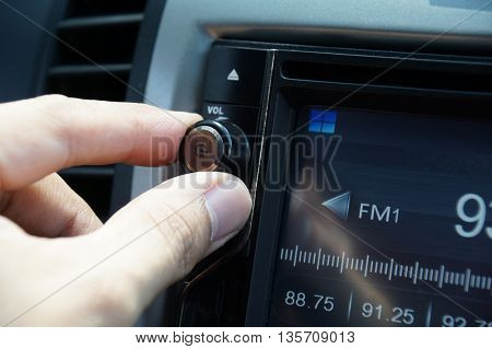 Left hand adjusting a volume control knob of the car's audio system. poster
