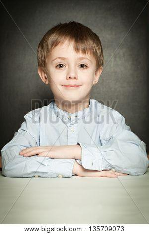 Happy little boy sitting in school classroom