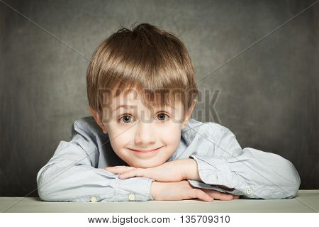 Cute schoolboy looking and smiling on grey background