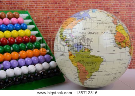 Globe and abacus side by side with a mud-brick wall background