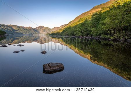 Perfectly symmetric reflections on a mirror-like lake at sunrise, rocks in foreground