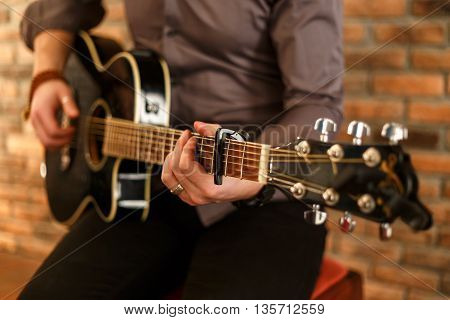 man playing the guitar with a capo