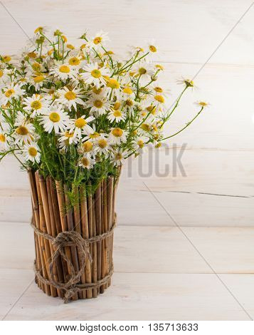 Daisies in a bamboo vase on a wooden surface.