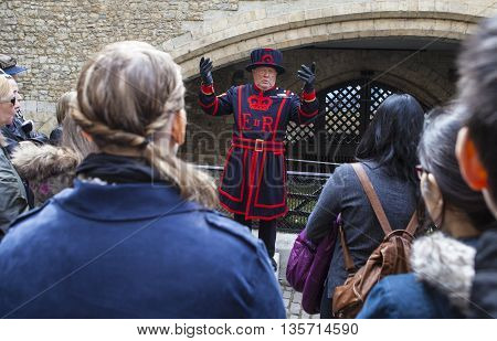 LONDON UK - APRIL 10TH 2016: A Yeomen Warder talking to visitors during a tour of the historic Tower of London on 10th April 2016.