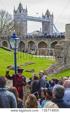 LONDON UK - APRIL 10TH 2016: A Yeomen Warder talking to visitors during a tour of the historic Tower of London on 10th April 2016. Tower Bridge can be spotted in the background.