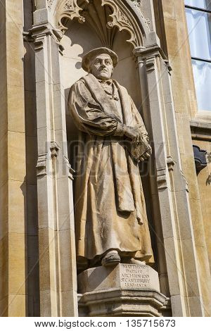 A statue of former Archbishop of Canterbury Matthew Parker on the exterior of Corpus Christi in Cambridge UK.