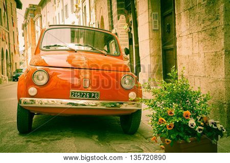 Gubbio, Italy - May 13, 2011; Retro effect iconic Italian orange car in grungy narrow street in small town.