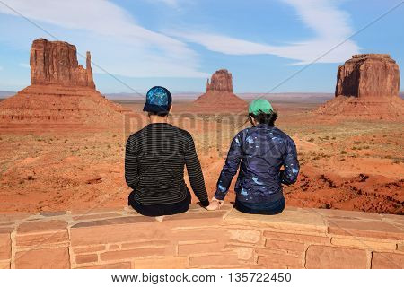 Couple of travelers taking picture with famous scenic spot. Monument Valley Arizona-Utah State line USA