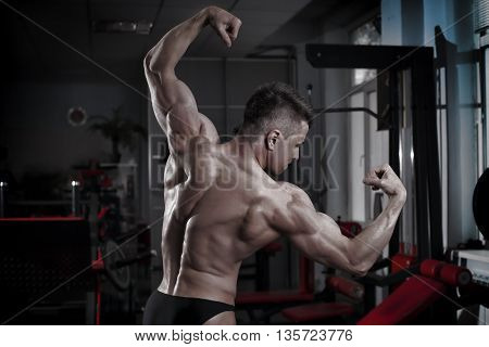 Bodybuilder posing in gym. Perfect muscular male back. Toning image