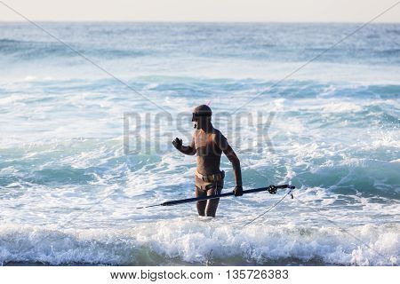 Diver with spear gun line buoy beach ocean swimming entry.