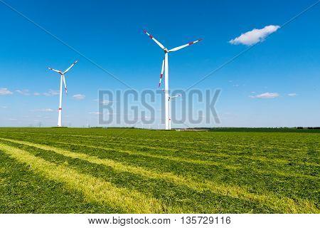 Windwheels in a mowed field of hay, seen in Germany