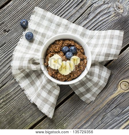 Healthy breakfast dessert. Chocolate Oatmeal with milk of oat bran with banana and blueberries for breakfast a la carte on a gray wooden background.