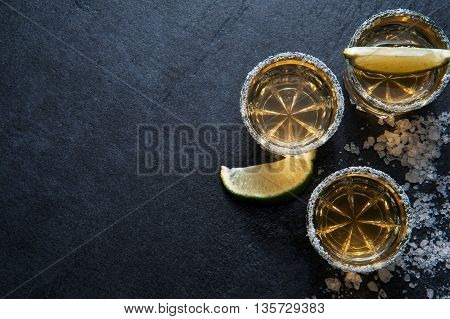Tequila shots with lime sliceand salt top view