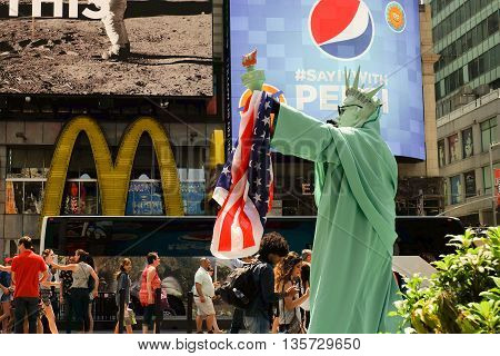 Manhattan, New York - June, 2016 living statue man performance as Statue of Liberty with American Flag at Times Square for celebrate before Independence Day of the United States, July 4th.
