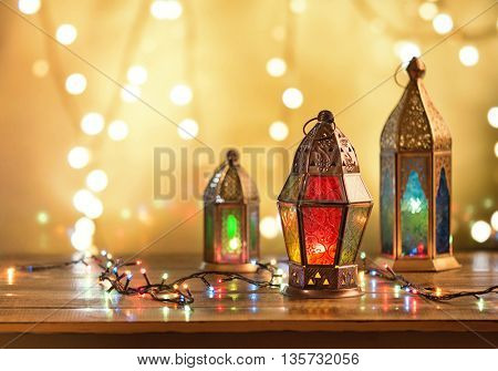 Various colorful Ramadan lamps lit up against illuminated decorative lighting background.