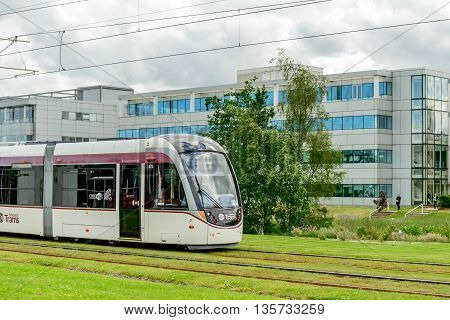 EDINBURGH SCOTLAND - JUNE 20 2016: A tramcar passing mordern office buildings at Edinburgh Park to the west of the city.