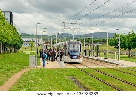 EDINBURGH SCOTLAND - JUNE 20 2016: Commuters boarding a tramcar service at Edinburgh Park to the west of the city.