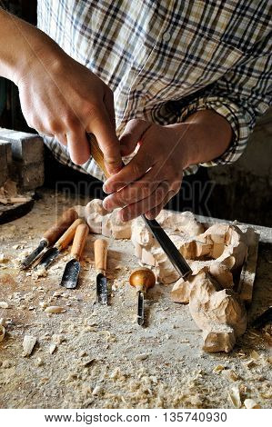 carver in workshop carving with manual chisel
