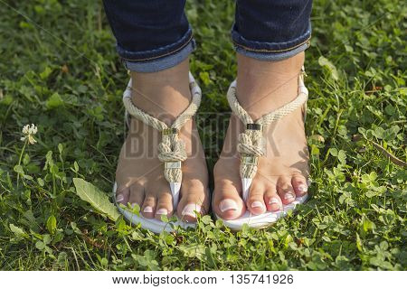 Feet girl in sandals with a beautiful pedicure on the green grass.