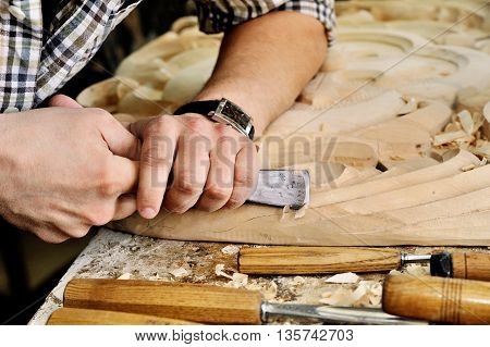 carvers Hands work with chisel in workshop
