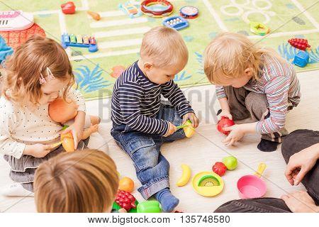 Children with teacher in kindergarten playing cooks