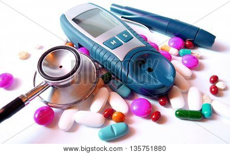 stethoscope,device for measuring blood sugar level and pills isolated on white background