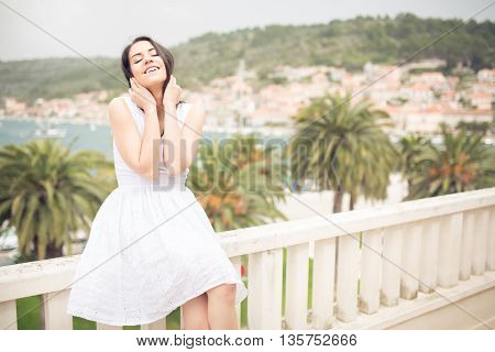 Happy smiling woman in white dress standing on villa terrace enjoying the summer holiday enjoying sun on her face.Finding your inner peace.Paradise vacation,resort relaxation