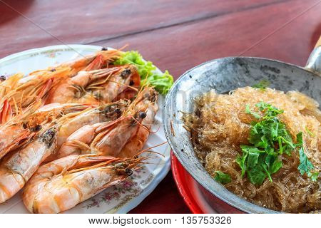 Top view steamed shrimp/prawn in the white plate and shrimps vermicelli with glass noodles in hot pot ready to eat