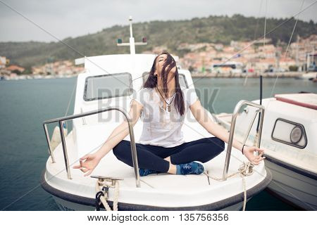 Young beautiful woman meditating on boat. Finding your inner peace. Meditation on Mediterranean Sea. Girl enjoying her earned vacation.Fun,relaxation and mindfulness concept