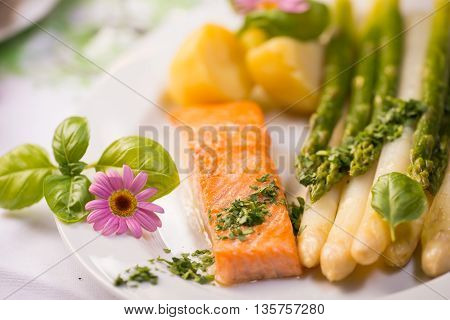 Salmon fillet with green asparagus and edible flowers