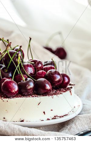Vanilla bavarian mousse cake with cherries and dark chocolate. Made with cream cheese and whipped cream. White plate and light background. poster
