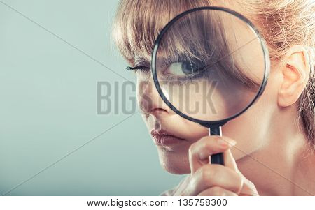 Investigation exploration education concept. Closeup funny woman face girl holding on eye magnifying glass loupe