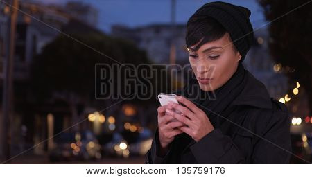 Fashionable Woman In Black Overcoat On Urban City Street At Night Using Texting App On Cell Phone