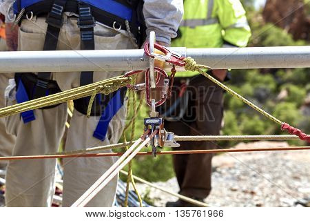 Close up of ropes and pulleys for rescue workers to climb down the side of the cliff. poster