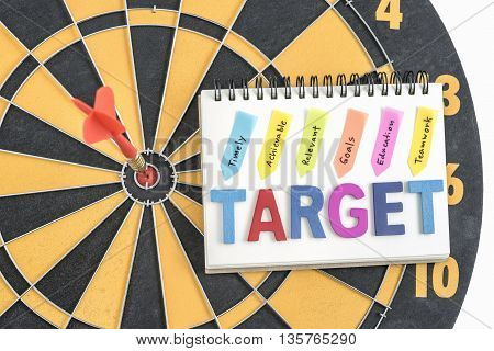 Arrow target in bullseye with alphabet letters words target on the notebook with handwriting timely achievable relevant goals education teamwork over dartboard background, Business marketing concept