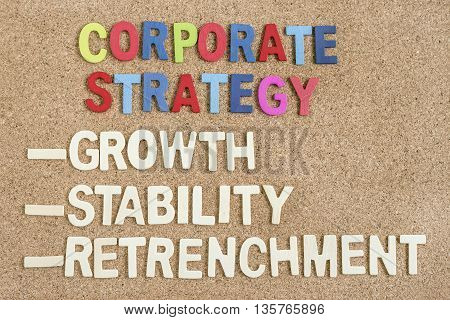 Alphabet wood letters of corporate strategy growth stability retrenchment words on wooden board, Top view, Strategy business concept
