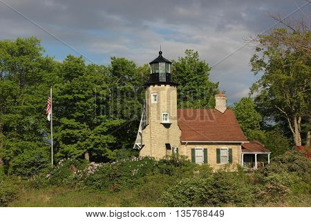 Historic Whitehall Lighthouse Station Museum in Spring with weather front passing thru